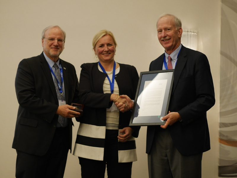 Mark Reichardt, OGC President & CEO, (left) and Jeff Harris, Chairman of the OGC Board of Directors, (right) present Marie-Françoise Voidrot with the 2017 Gardels Award.
